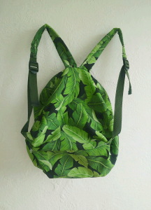 Back view of a small backpack with a green leafy pattern